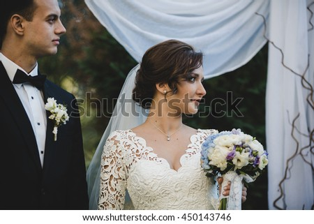 Brunette bride with curly hair looks over her shoulder standing behind a wedding altar