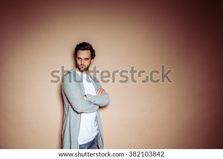 Brunette brown haired man with beard and white t-shirt and grey hoody in front of beige studio backdrop