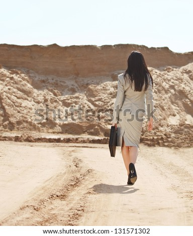 Brunette business woman walking away in a desert - stock photo