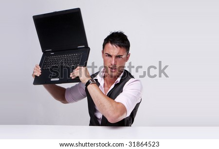 Brunette businessman holding a laptop trying to destroy it , problems at work