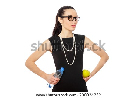 brunette businesswoman in black dress holding apple and bottle of water over white background. healthy lifestyle  - stock photo