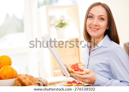 Brunette businesswoman is reading the newspaper while having breakfast at home - stock photo
