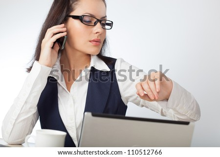 brunette businesswoman looking at her watch - stock photo