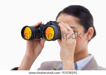 Brunette businesswoman looking through binoculars against a white background - stock photo