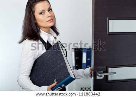 brunette businesswoman opening the dark brown door