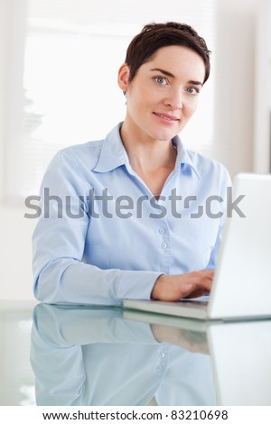 Brunette businesswoman with a laptop looking at the camera in an office - stock photo