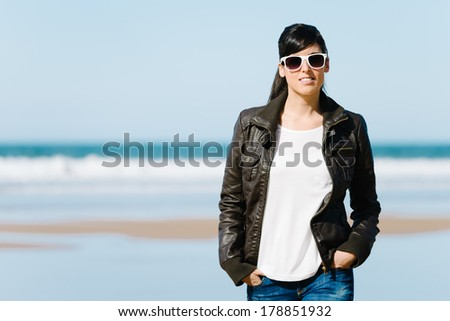 Brunette casual woman with sunglasses walking on the beach. Hispanic relaxed female with leather jacket. - stock photo