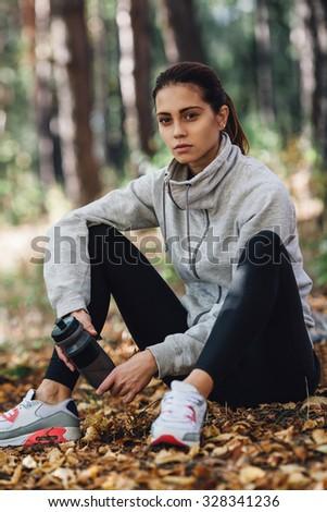 brunette caucasian runner woman rest on the leaves in park - stock photo