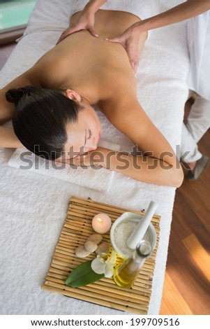 Brunette enjoying a massage with beauty treatments beside at the health spa - stock photo