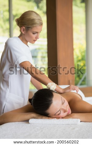Brunette enjoying a peaceful massage with eyes closed at the health spa - stock photo