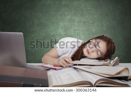 Brunette female high school student sleeping in the class above the book with laptop on the table