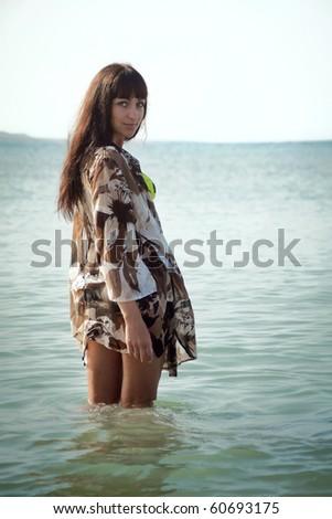 Brunette female in a beach dress standing in ocean water. Shot from back in a half-turn. Tenerife, Spain. - stock photo