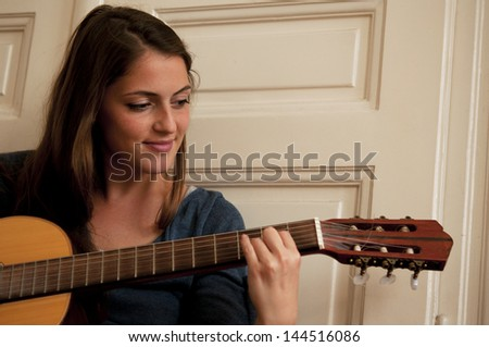 Brunette female playing acoustic guitar - stock photo