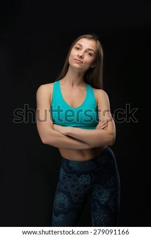 Brunette fitness woman folded her arms. In the studio, isolate on a dark background. - stock photo