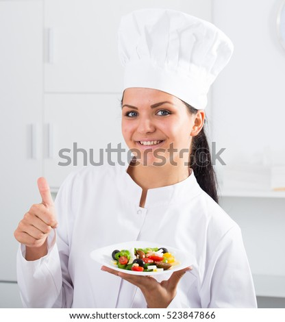 Brunette girl chef showing thumbs up and plate with salad