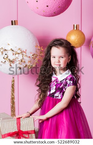 Brunette girl child 5 years old in a pink dress. in holiday rose quartz room with gifts.