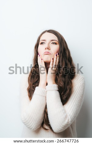 Brunette girl confused on a white background - stock photo