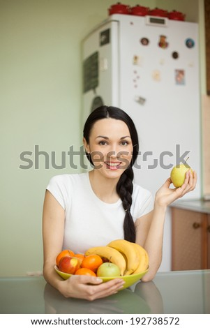 brunette girl holding dish with fruits sitting in the kitchen