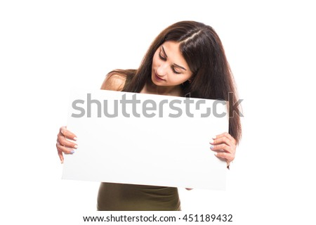 Brunette girl in a green dress with a white sign for your text, isolated on white background.
