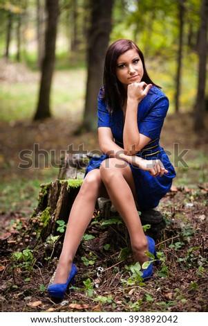 Brunette girl in blue dress at park. - stock photo