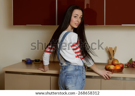 Brunette girl in home clothes standing near a kitchen cupboard in half a turn. She is dressed in blue overalls and a white shirt. Behind her is a kitchen furniture painted in beige and maroon tones. - stock photo