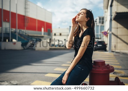 Brunette girl in rock black style, standing outdoors in the city street