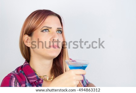 Brunette girl is enjoying her blue Martini cocktail on a couch.