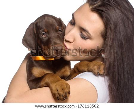 Brunette girl kissing her doberman puppy isolated on white background - stock photo