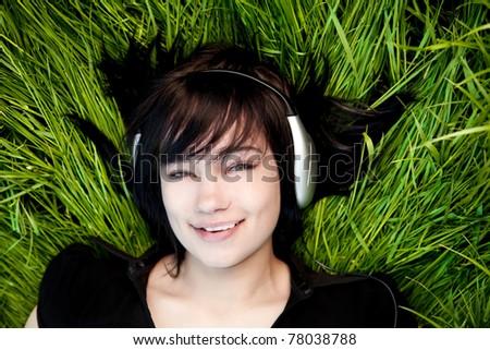 Brunette girl listening music at green grass. - stock photo