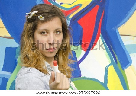 Brunette girl posing against a colorful backdrop holding lipstick