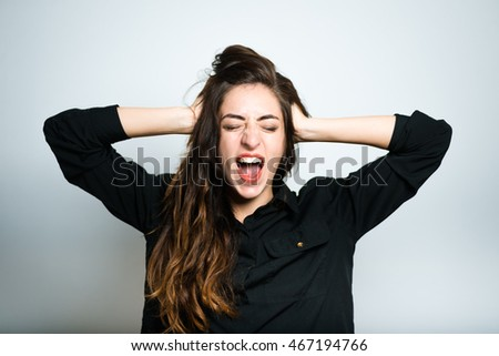 brunette girl shouting angry, dressed in black, isolated on white background