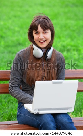 Brunette girl sitting at the bench with notebook - stock photo