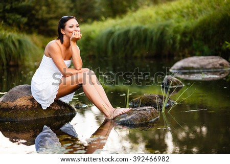 Brunette girl sitting on stone at pond. - stock photo