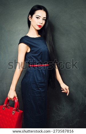 Brunette girl wearing a blue dress and a red bag in his hands - stock photo