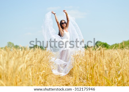 Brunette girl wearing white dress standing in golden wheat field over blue sky background. Young woman raised hands and wind blowing her dress. - stock photo