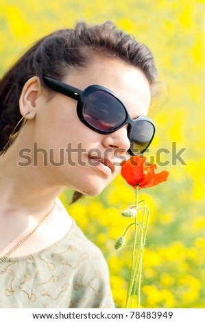 Brunette girl with a corn poppy in her hand, on a blooming rapeseed field