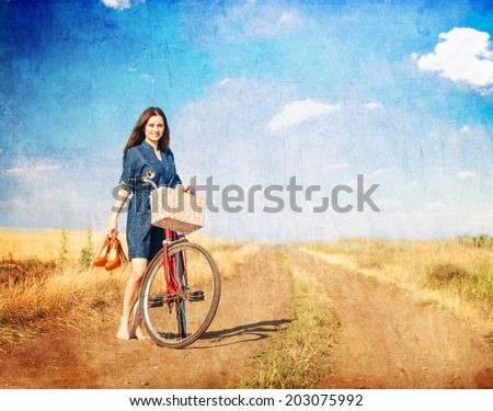 Brunette girl  with  bicycle on countryside road. - stock photo
