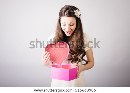 Brunette girl with gift for Valentines Day. Photo with light background