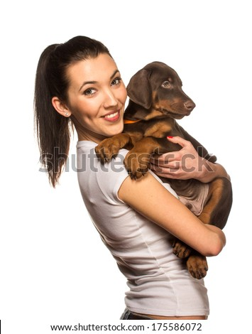 Brunette girl with her doberman puppy isolated on white background - stock photo