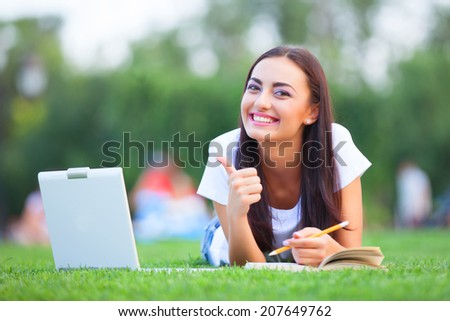Brunette girl with notebook and book on green grass in the park. - stock photo