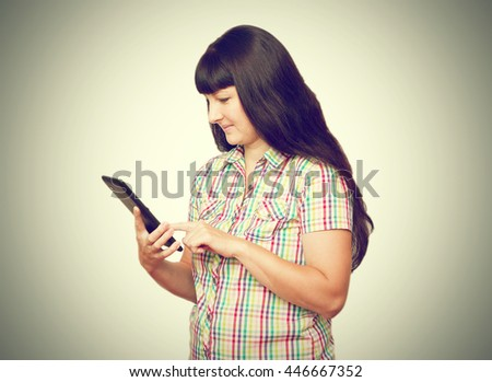 Brunette girl with rabusename hair holding a tablet computer. Isolated on a white background. - stock photo