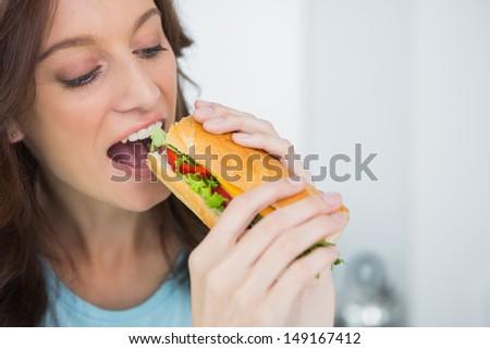 Brunette having lunch break in her kitchen - stock photo