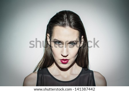 Brunette high fashion model portrait at wall - stock photo
