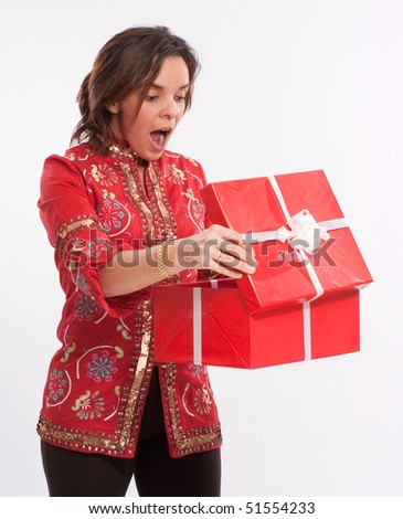 Brunette in red opening a gift box of the same color - stock photo