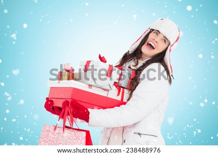 Brunette in winter clothes holding many gifts and shopping bags against blue vignette - stock photo