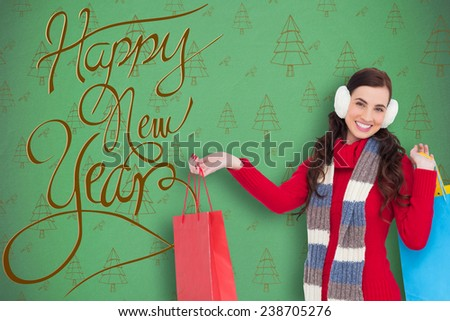 Brunette in winter clothes holding shopping bags against green christmas tree pattern - stock photo