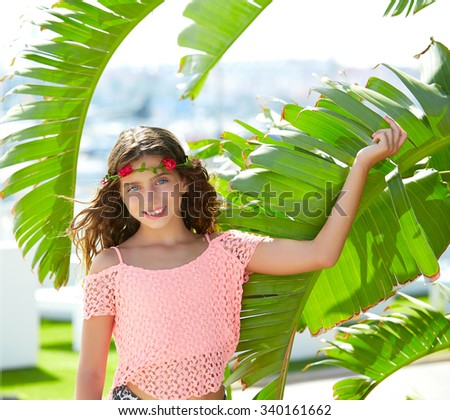 Brunette kid girl at banana tree leaves in bright day light in Mediterranean - stock photo