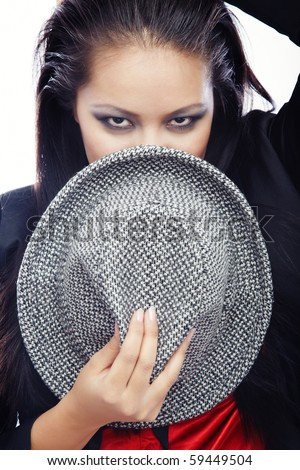 Brunette lady holding hat and covering face on a white background