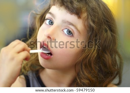 brunette little girl eating  plastic spoon