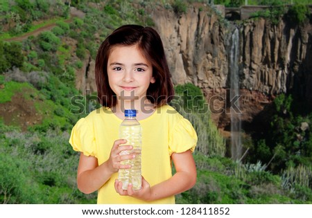 Brunette little girl with a water bottle with a waterfall of background - stock photo